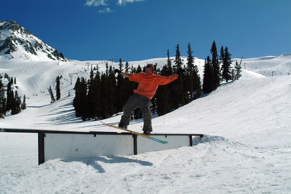 A snowboarder does a frontside rail slide at Arapahoe Basin.
