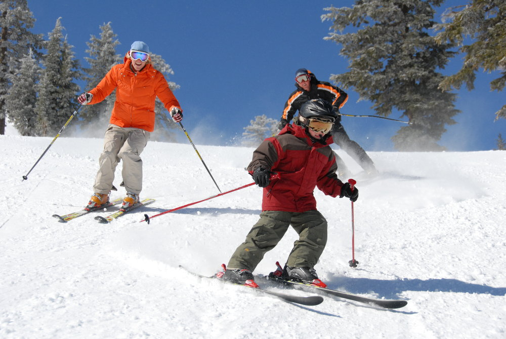 Three skiers enjoy a run at Sugar Bowl Ski Resort, California
