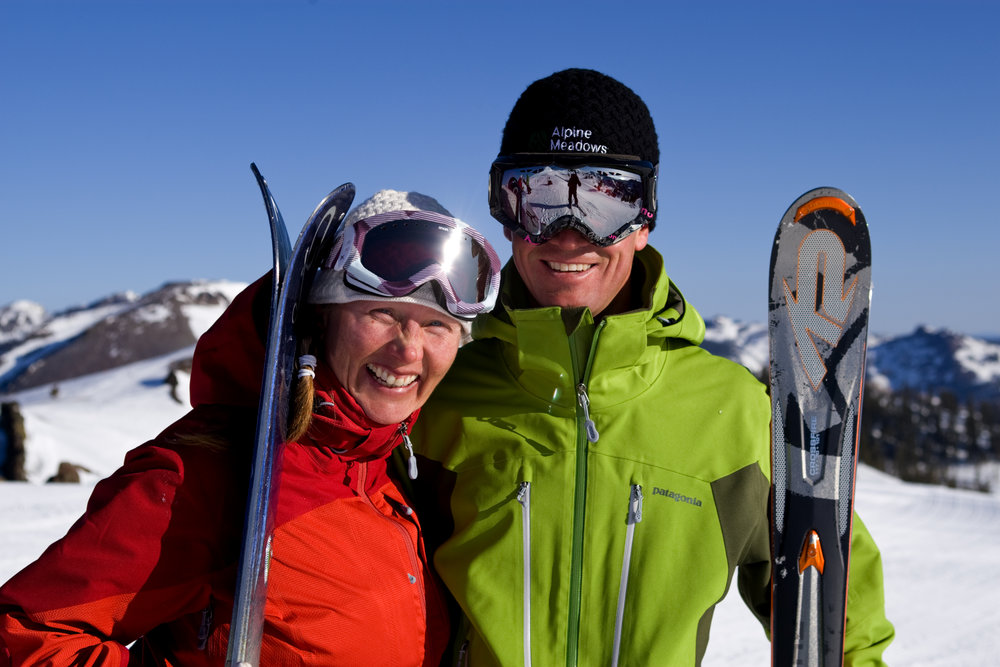 Two skiers pose for a photo atop Alpine Meadows, California