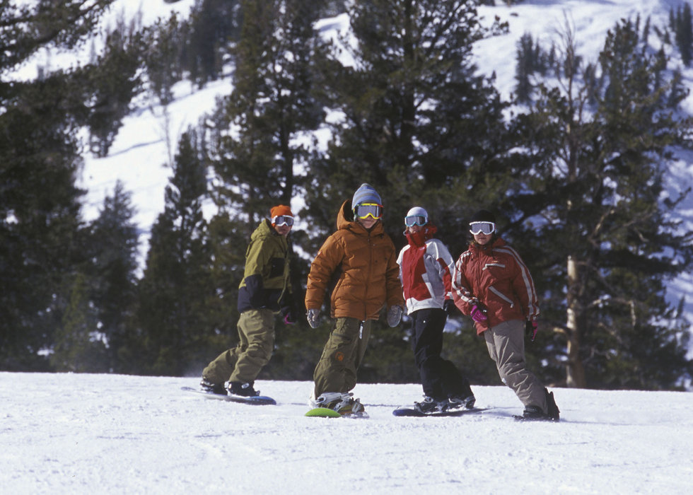 Four snowboarderscruise down a run in Mammoth Mountain, California