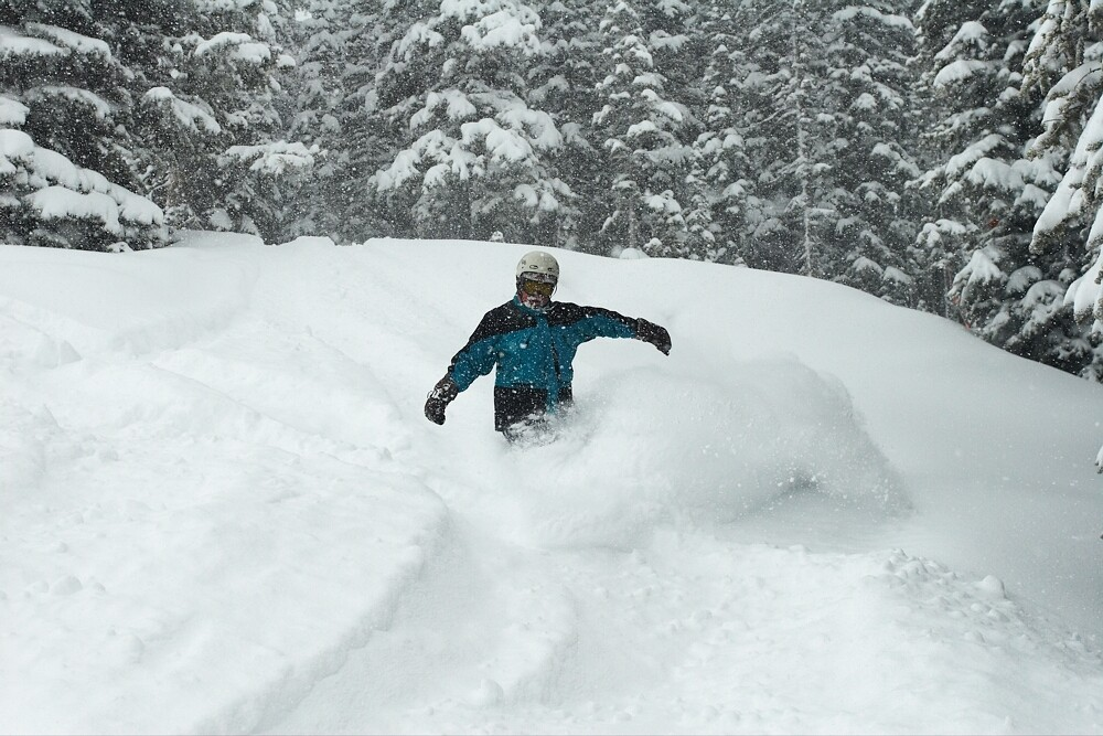A snowboarder in powder at Aspen Mountain, Colorado