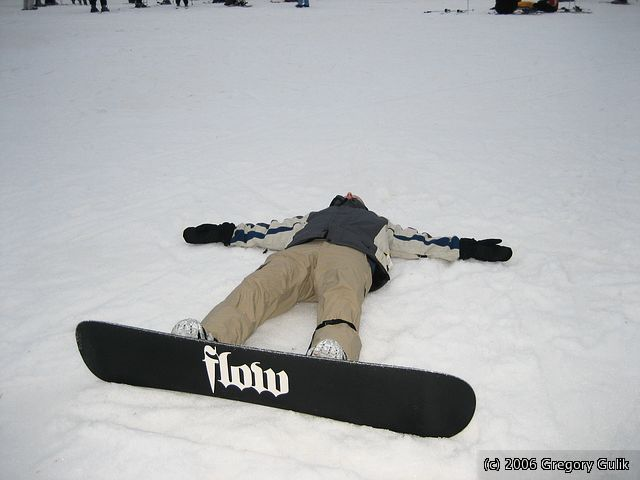 A snowboarder lays in the snow at Cascade Mountain, Wisconsin