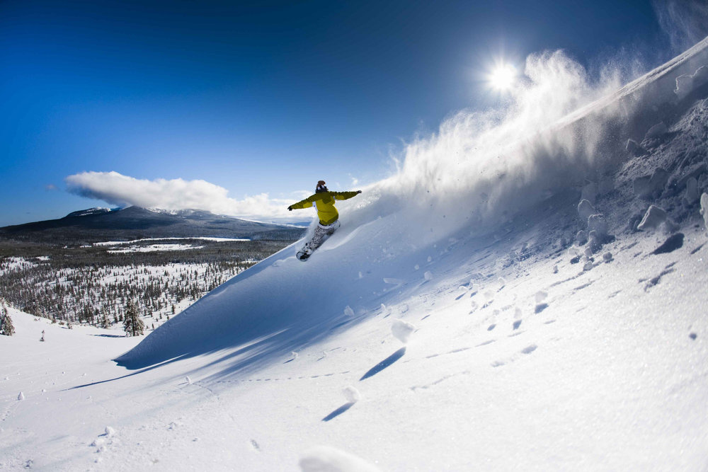 Snowboarder cresting a pow wave at Hoodoo.