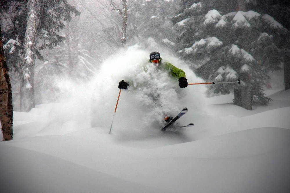 A skier bursting through powder at Le Massif, Quebec, Canada.