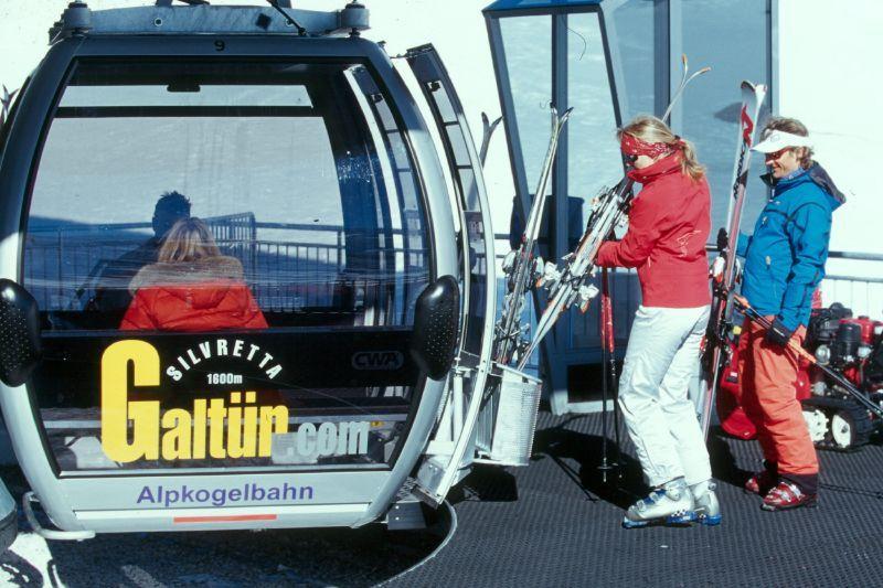 Skiers boarding a mountain gondola at Galtur
