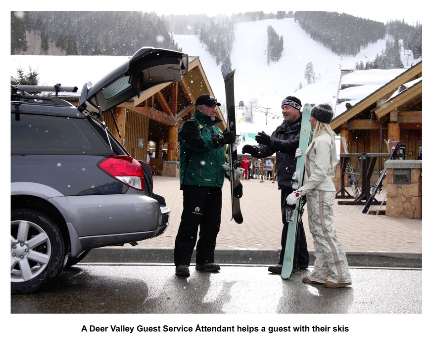 A Deer Valley Guest Service Attendant helps a guest with their skis.