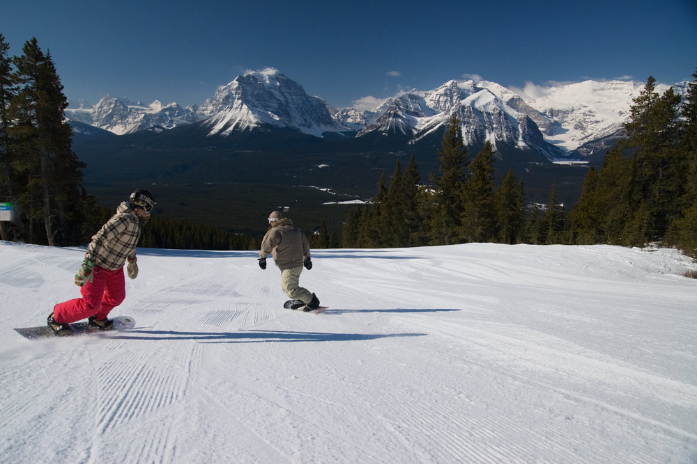 Snowboarders on wide piste at Lake Louise, Banff