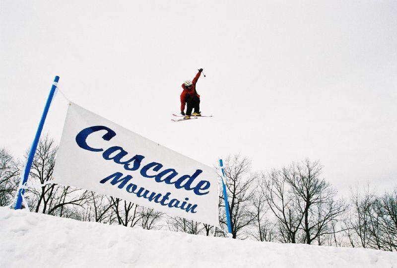 A skier jumps over a sign at Cascade Mountain, Wisconsin