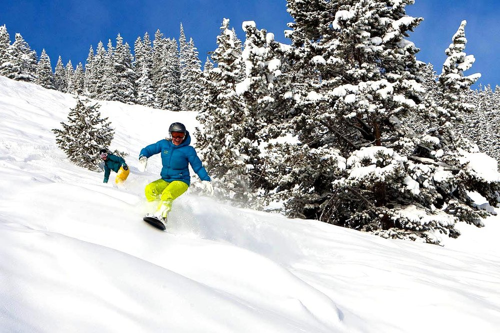 Snowboarders play in a foot of fresh powder at Aspen Mountain.