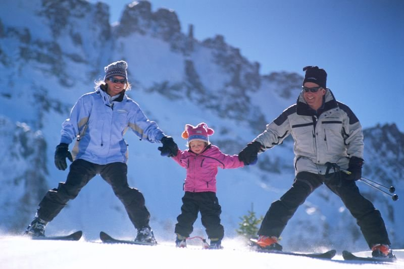 A mother and father take their child slowly down a run in Telluride, Colorado