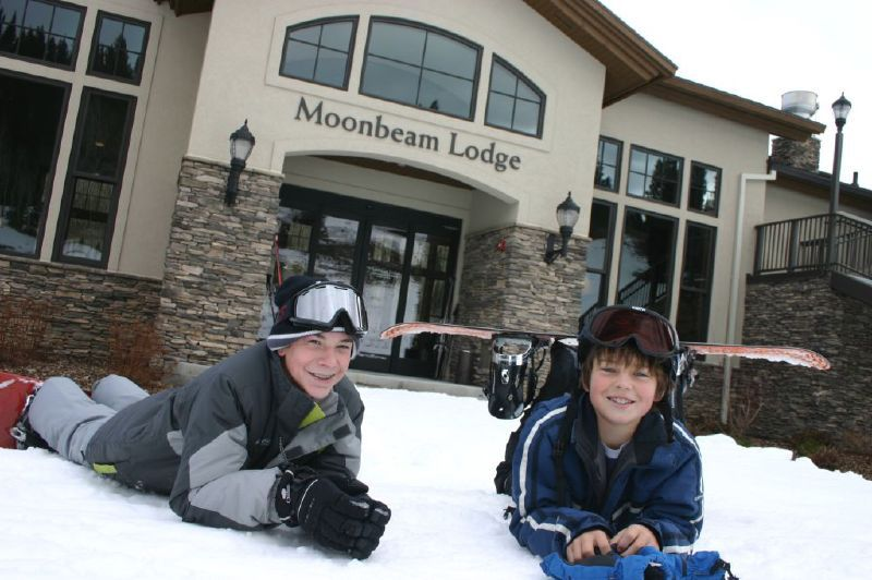 Two boys in front of the Moonbeam Lodge in Solitude Mountain Resort, Utah