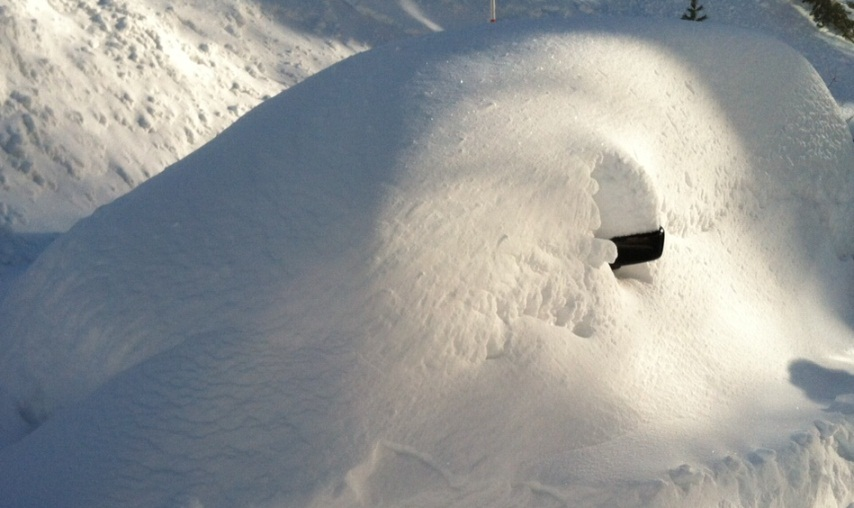 A car sits buried in by weekend snow in the parking lot of Squaw Valley.