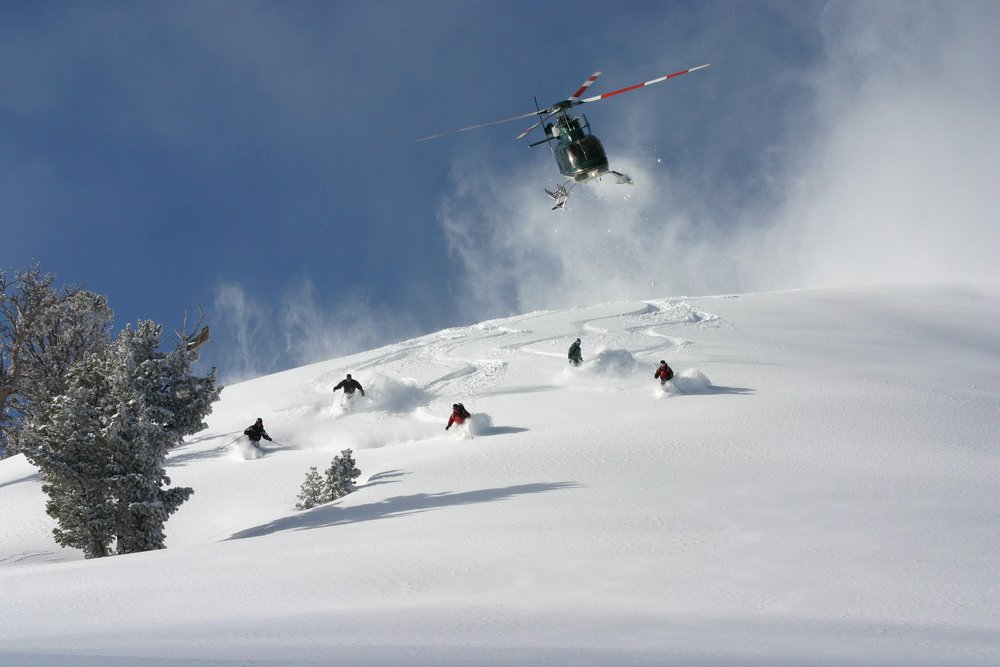 The chopper blasts away above some eager shredders at High Mountain Heli-skiing.