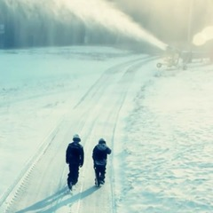 Snowmakers walk out to check on one of the guns.