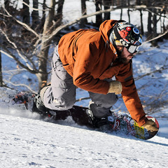 A snowboarder carving hard. Photo Courtesy of Canaan Valley Resort.