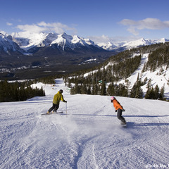 Snowboarders descend a groomer at Lake Louise.