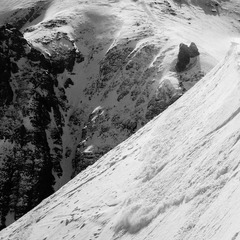 A tender wind slab breaks away as Herb Manning hikes for some turns at Telluride.
