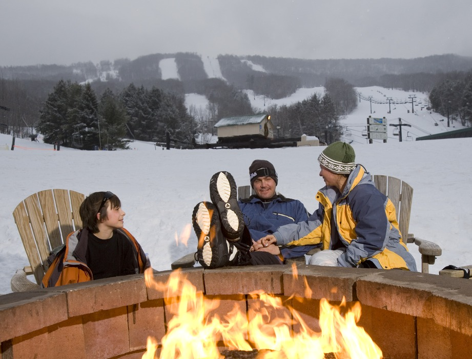 A family relaxes around the fire pit at Windham Mountain, New York