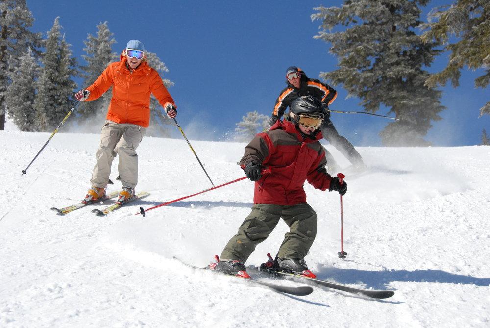Three skiers enjoy a run at Sugar Bowl Ski Resort, California