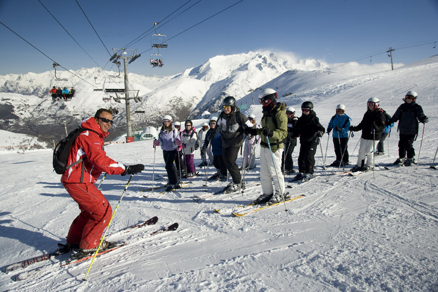 "Ski instructor teaching a group the all-important ""bend your knees"" on the mountain. - © James Young"