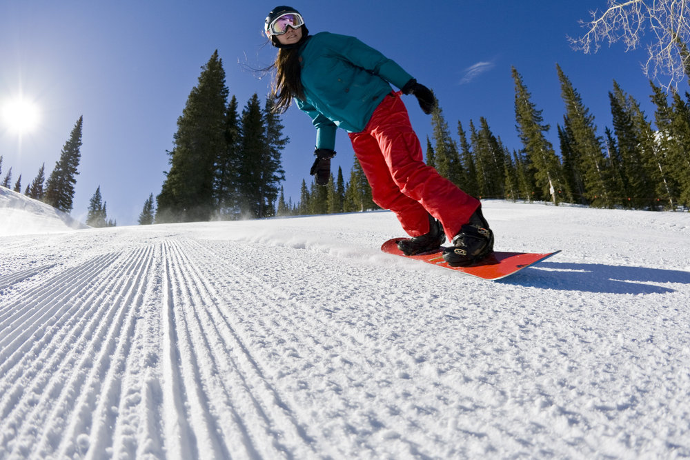A snowboarder shreds the corduroy on Aspen Mountain. - ©Photos courtesy The Little Nell.