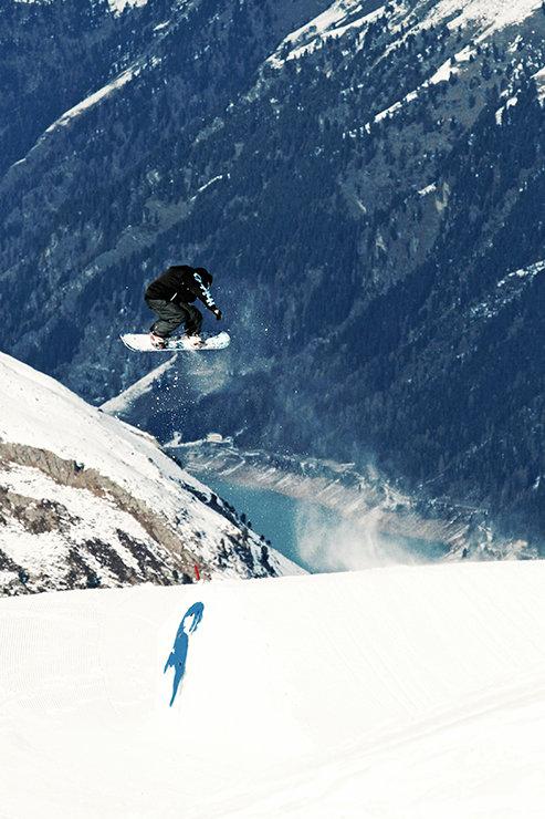 Snowpark Kaunertal: Backisde 360 über den Pro Kicker mit Blick auf den Gepatsch Stausee - © Stefan Drexl