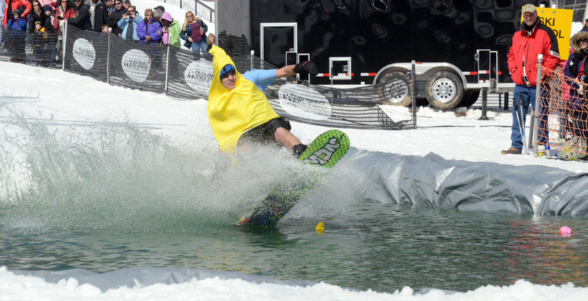 A costume-clad skier skims the pond at Seven Springs. - © Seven Springs