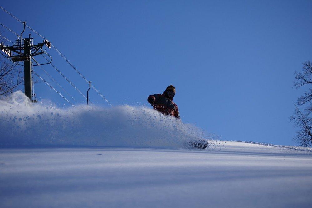 A snowboarder carves a wave of fresh powder at Blackjack. - © Blackjack Ski Resort