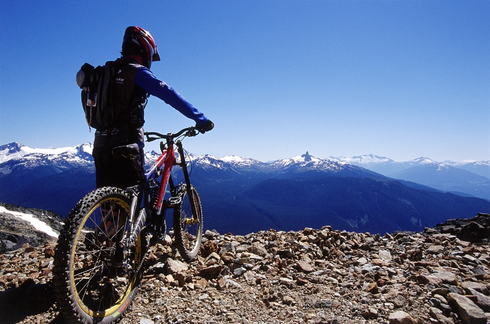 Mountain biker looking over the edge of a mountain in Whistler