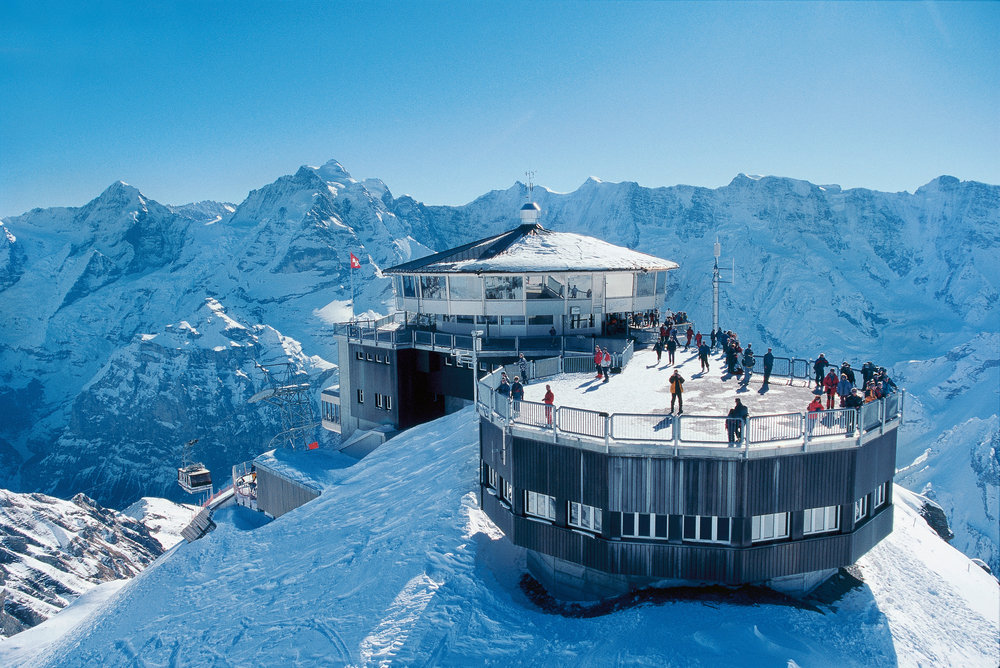 Switzerland. get natural. The revolving restaurant 007 Piz Gloria on top of the Schilthorn (2,970 m) high above Muerren in the Bernese Oberland. In the background the Moench, Jungfrau and Gletscherhorn. Schweiz. ganz natuerlich. Das Drehrestaurant 007 Piz Gloria auf dem Schilthorn (2970 m) o