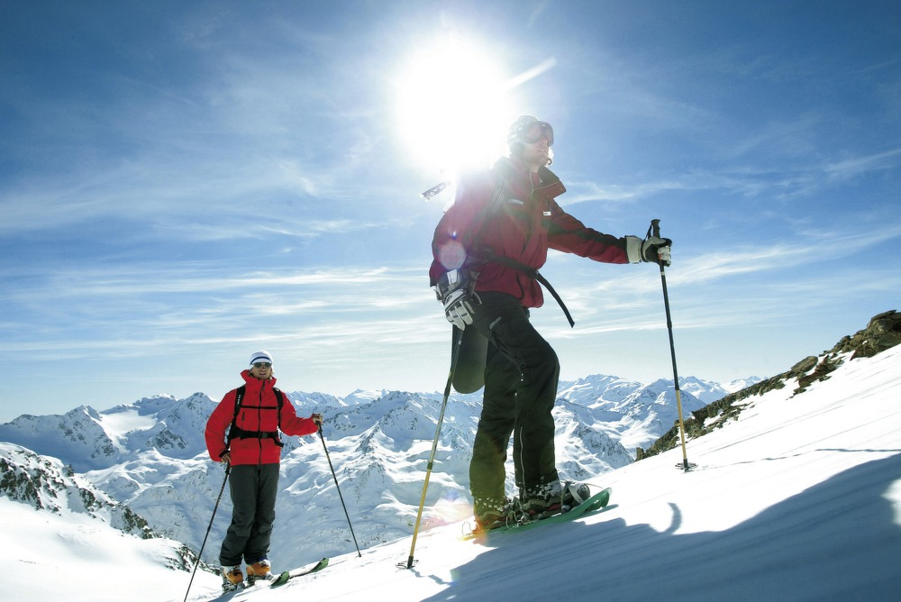 Couple snowshoeing in Stubai with sun behind them