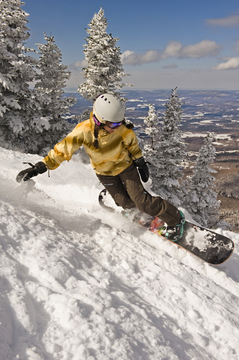 A snowboarder turning on mountainside at Smugglers' Notch, Vermont.