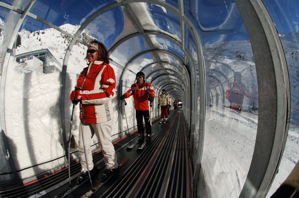 Visitors to St. Anton, Austria in covered conveyor lift.