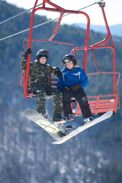 Snowboarding kids on lift at Cranmore, NH.