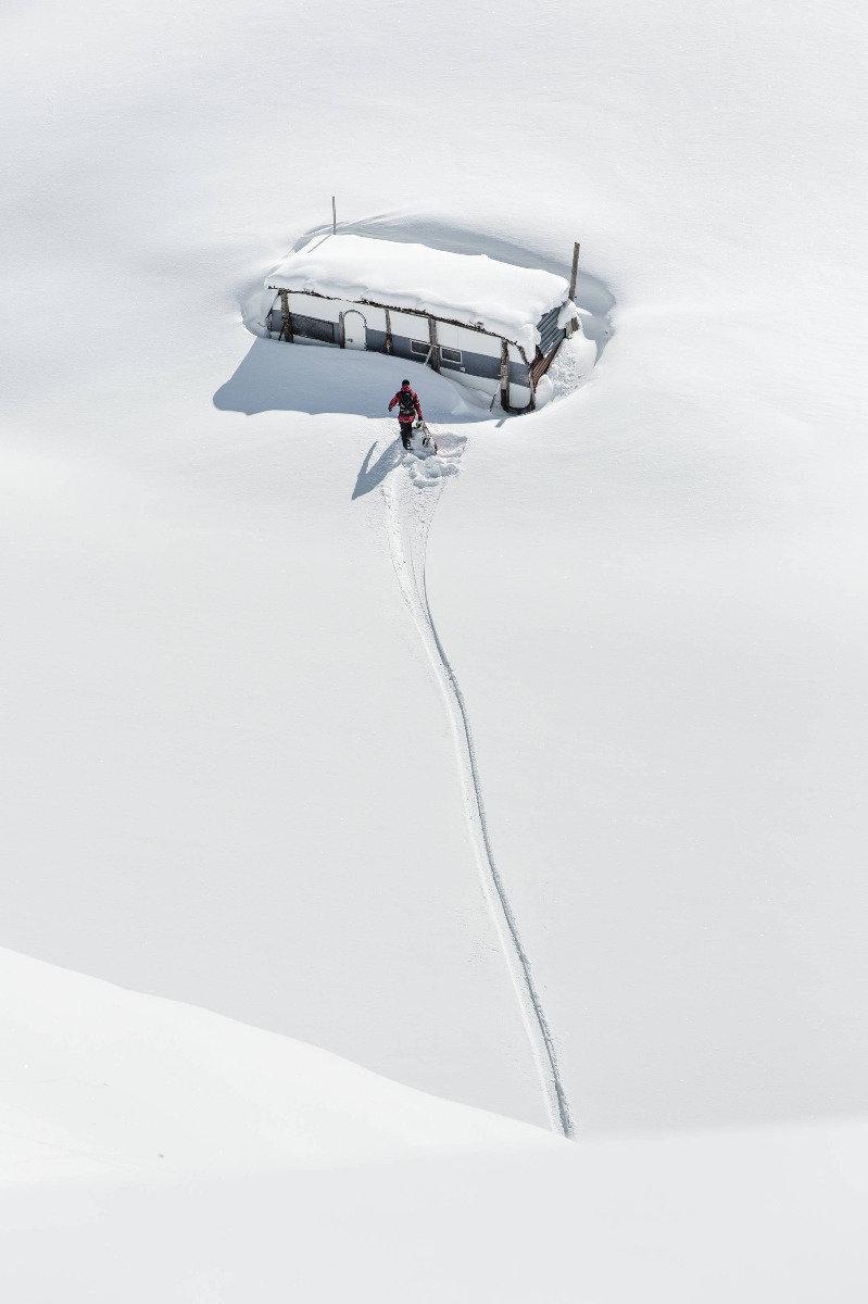 Philipp Schicker unterwegs zu seinem eingeschneiten Wohnwagen in Hoch-Ybrig - ©Red Bull Illume | Claudio Casanova