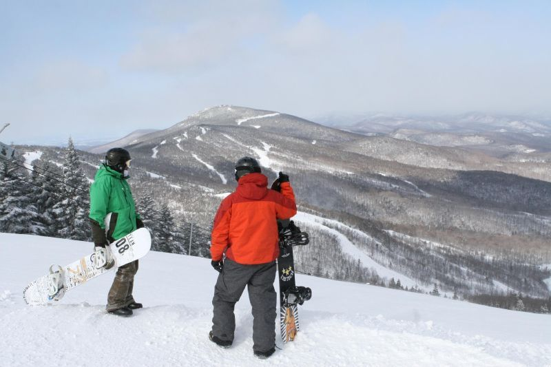 A pair of snowboarders pause atop Killington.