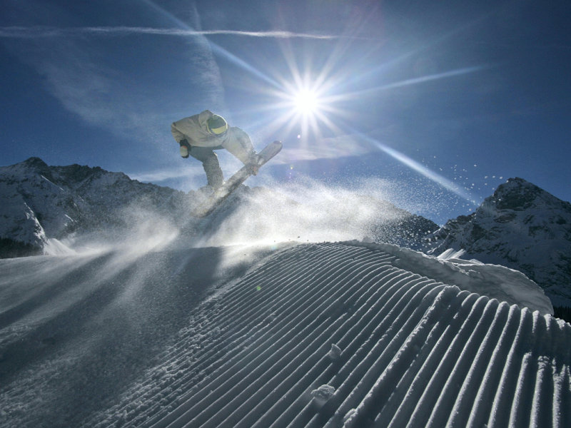 A snowboarder on groomed slopes at Ehrwald, Austria.