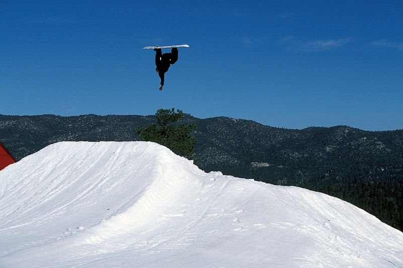 A snowboarder does a flip off jump in Snow Summit, California