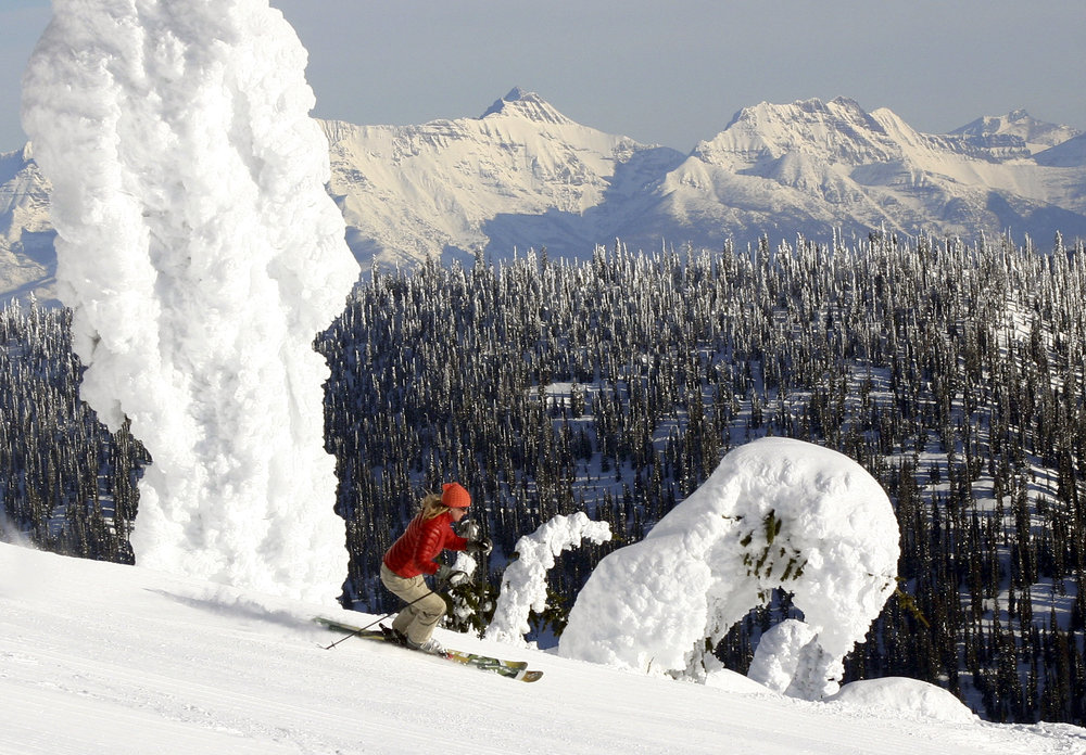 A skier carves by the famous snow ghosts at Whitefish Mountain Resort, with the peaks of Glacier National Park in the distance.  - © Brian Schott/Whitefish Mountain Resort