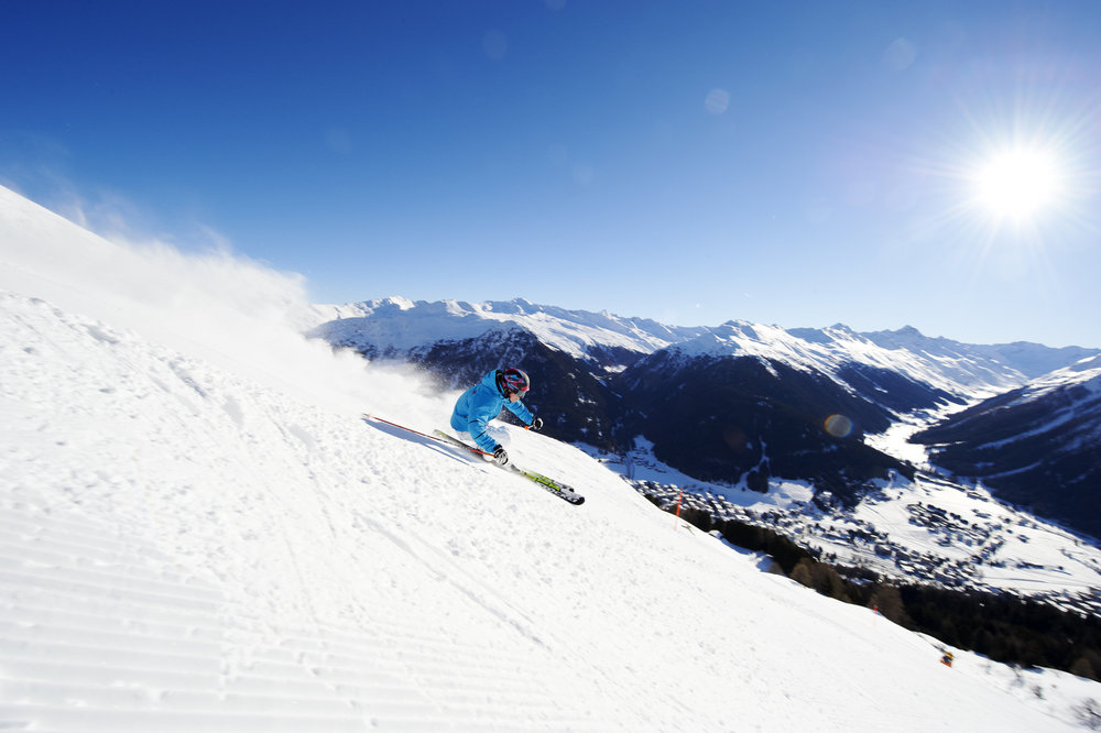 Skier carving above Davos village, Switzerland (Davos Klosters Tourism)