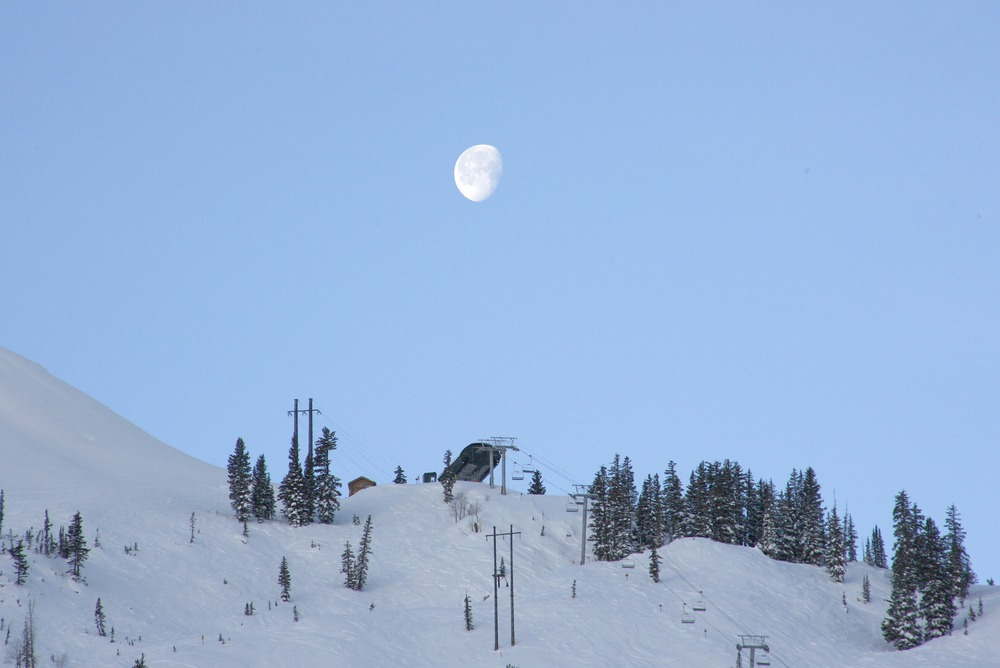 The moon visible in the clear sky over Brighton, Utah.
