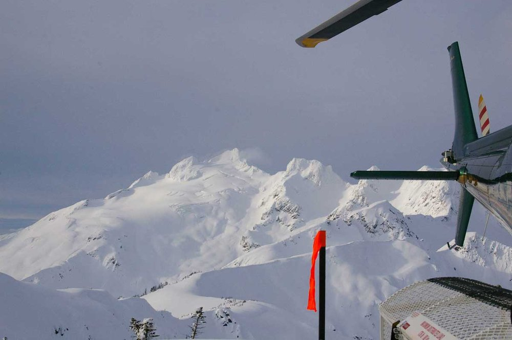 The chopper with awesome terrain in the background with Northern Escape Heli-Skiing. - ©Northern Escape Heli-Skiing