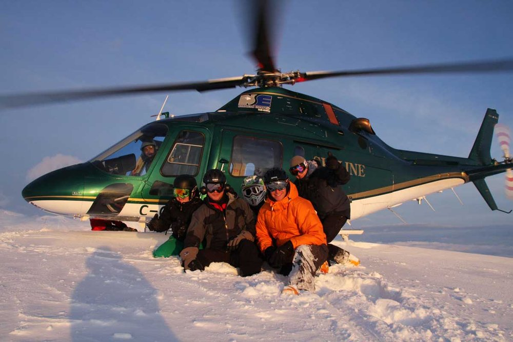 Satisfied customers in front of the chopper at Northern Escape Heli-Skiing. - ©Northern Escape Heli-Skiing