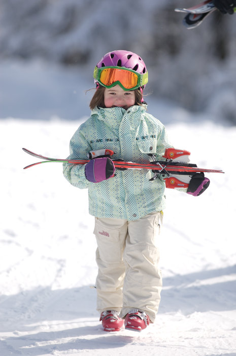 A little girl carries her skis at Mount Sunapee