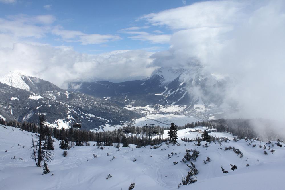 Blick hinab zum Bergrestaurant Grubigalm. Im Hintergrund die Südhänge der Zugspitze in Wolken. - © Skiinfo.de