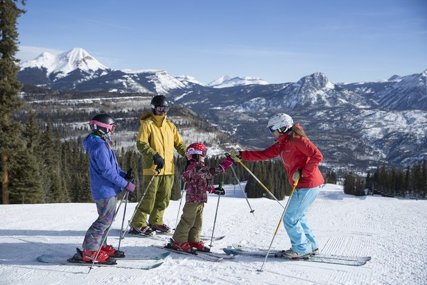 Family enjoys quality time together on the slopes with breathtaking views of the Colorado Rockies.
