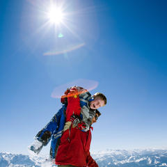 Vader en zoon spelen in de sneeuw in het zonnige Tauplitz