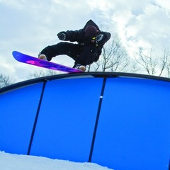 A snowboarder gets low on the rainbow rail in the park at Mount Sunapee. Photo courtesy of Mount Sunapee.