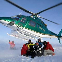 Satisfied customers in front of the chopper at Northern Escape Heli-Skiing.